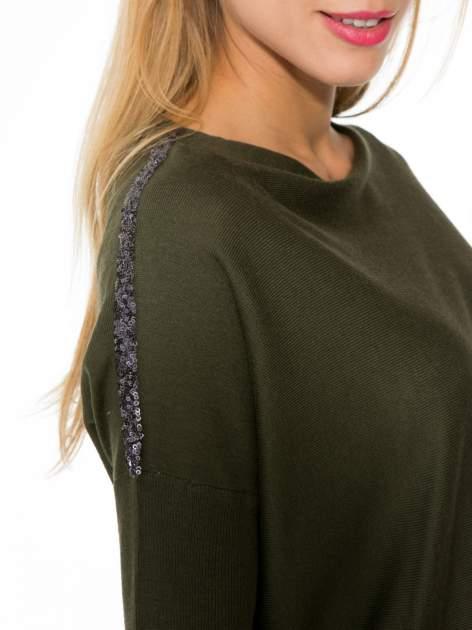 Oliwkowy sweter o nietoperzowym kroju z cekinową aplikacją na rękawach                                  zdj.                                  8