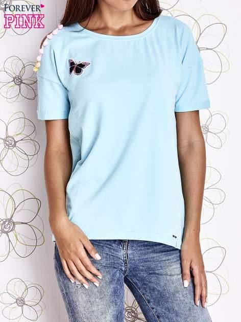 Turkusowy t-shirt z naszywką motyla i pomponikami                                  zdj.                                  1