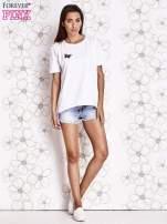 Biały t-shirt z naszywką motyla i pomponami