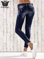 Ciemnoniebieskie spodnie rurki z dekatyzowaniem i przetarciami                                  zdj.                                  2