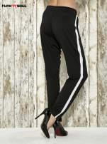 Czarne spodnie materiałowe z białym lampasem                                  zdj.                                  2