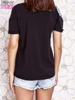 Czarny t-shirt z naszywką motyla i pomponami