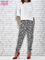 Granatowe zwiewne spodnie alladynki we wzór kwiatków                                  zdj.                                  2