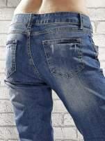 Niebieskie spodnie skinny jeans z postrzępioną nogawką na dole                                  zdj.                                  5