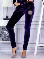 Spodnie dresowe welurowe z błyszczącymi kamyczkami fioletowe                                  zdj.                                  1