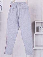 Szare spodnie dresowe dla dziewczynki z taśmą tricolor                                  zdj.                                  2