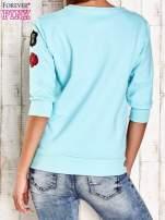 Turkusowa bluza z naszywkami na rękawie