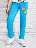 Turkusowe spodnie dresowe dla dziewczynki z nadrukiem serc                                  zdj.                                  1